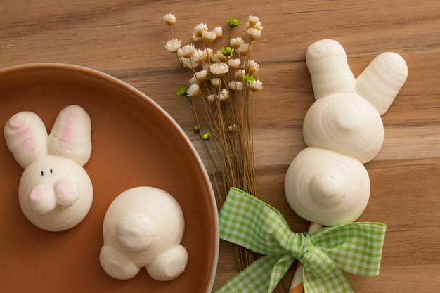 Cute easter bunny meringues on wooden background