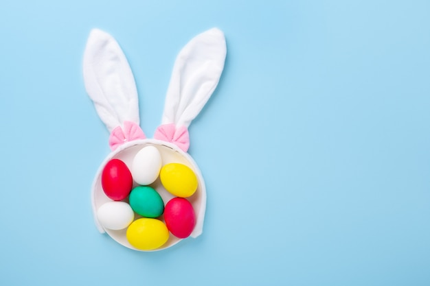 Cute easter composition. multicolored easter eggs and bunny ears on blue background. top view. copy space