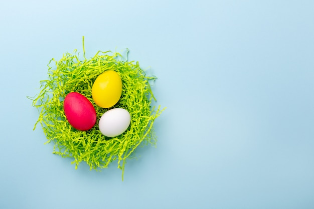 Cute easter composition. paper nest with multicolored easter eggs on blue background. top view. copy space