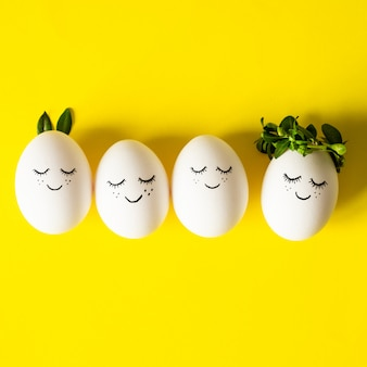 Cute easter eggs with a painted face in a spring leaves on yellow background. happy easter.