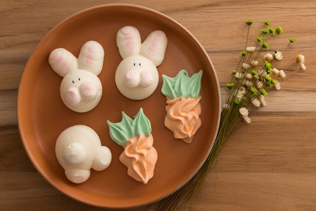 Cute easter meringues on wooden background