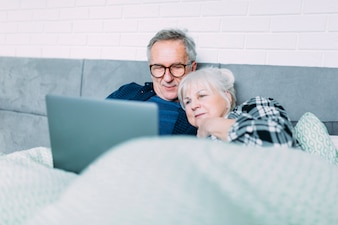 Cute elderly couple in bed with laptop