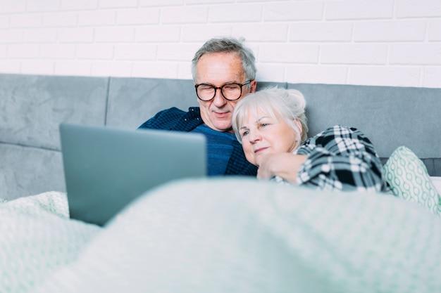 노트북으로 침대에서 귀여운 노인 부부