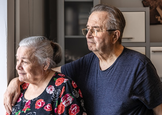 A cute elderly couple stands at the window and looks out for someone, waiting.