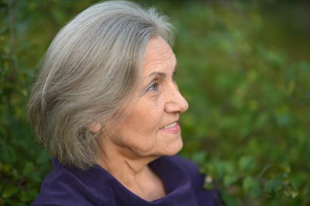 公園を歩くかわいい年配の女性