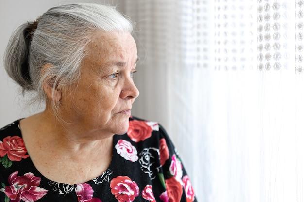 Милая пожилая женщина с грустью смотрит в окно копирования пространство.
