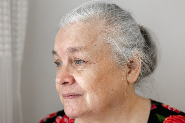 Carina donna anziana con tristezza guarda fuori dalla finestra da vicino.