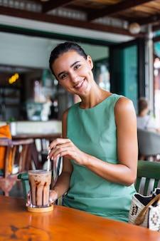 La donna felice calma elegante sveglia in vestito verde da estate si siede con il caffè nella caffetteria godendo la mattina