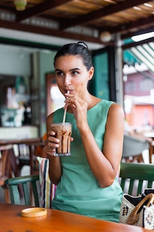 Cute elegant calm happy woman in green summer dress sits with coffee in cafe enjoying morning