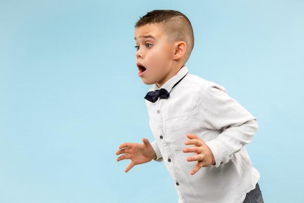 Cute elegant teen boy on blue background. emotional expression