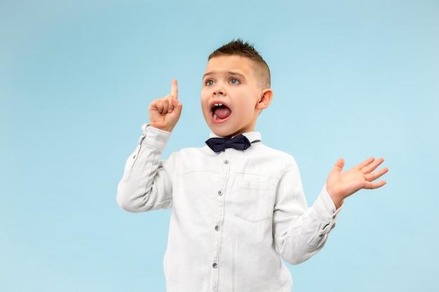青い背景のかわいいエレガントな十代の少年。感情的な表現