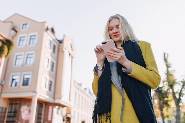 Carina donna bionda attraente emotiva in cappotto con smartphone cammina per la strada della città