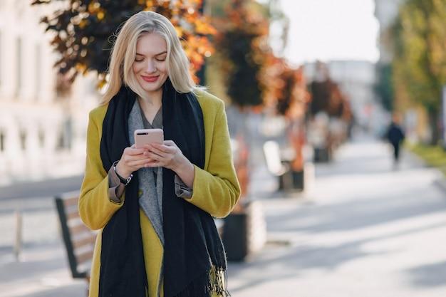 スマートフォンでコートを着たかわいい感情的な魅力的なブロンドの女性は、街を歩きます。散歩、ライフスタイル、通りの間のコミュニケーション。