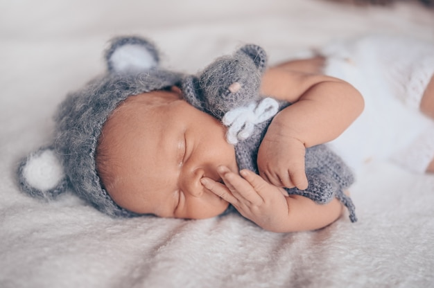 Cute emotional newborn infant baby boy sleeping in crib in a knitted suit with toy.