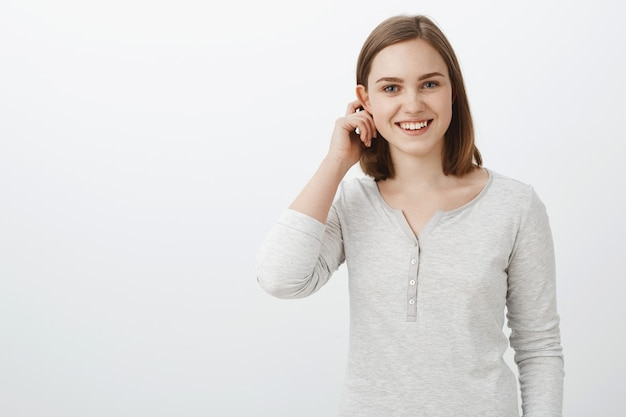 Cute emotive teenage girl in casual blouse flicking hair behind flapped ear and smiling broadly feeling shy and joyful being invited to play with interesting company over white wall