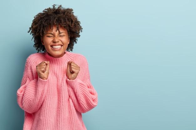 目標を達成し、良い結果を達成するために幸せなかわいい感情的な女性は、拳を握りしめ、幸せに笑う
