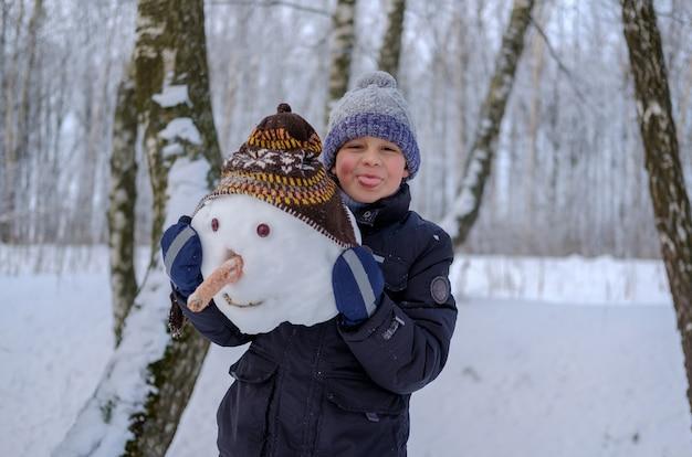 雪の中で冬の日に雪に覆われた森の中でかわいいヨーロッパの少年と面白い雪だるま