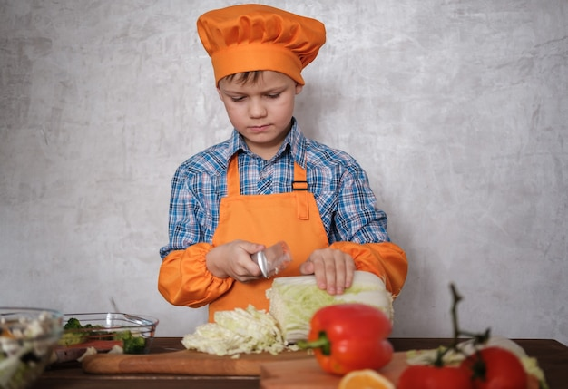 Cute european boy cuts chinese cabbage with knife on cutting board for vegetable salad