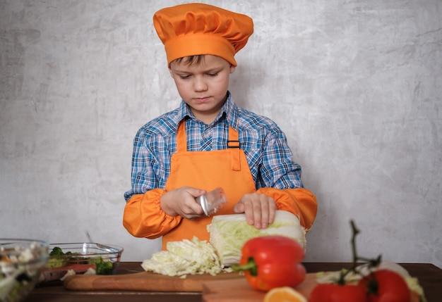 かわいいヨーロッパの少年は、野菜サラダのまな板にナイフで白菜を切る