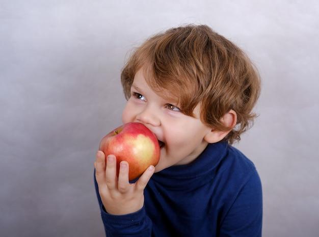 赤いリンゴを食べるかわいいヨーロッパの少年