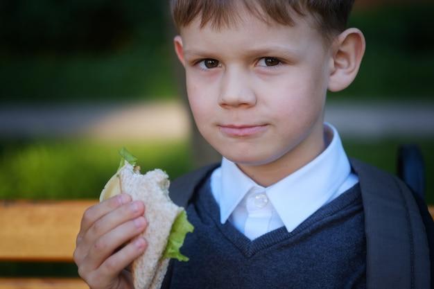Cute european boy eats school breakfast on the park bench after class