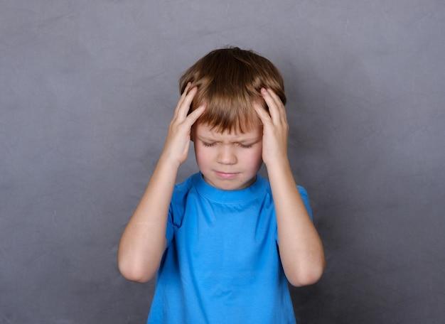 Симпатичный европейский мальчик, держащий руки за головой от боли