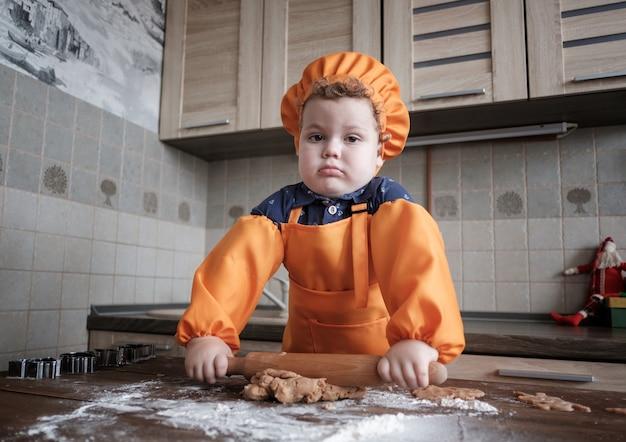 シェフの帽子とエプロンを着たかわいいヨーロッパの少年がテーブルのキッチンでジンジャークッキーを準備します
