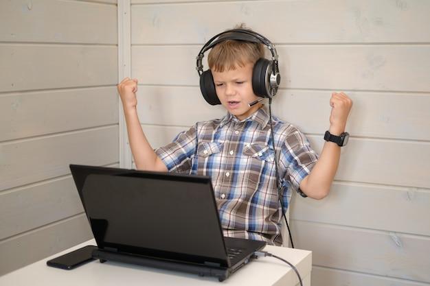 マイク付きのヘッドフォンでかわいいヨーロッパの少年は、ラップトップに座って喜んで手を上げます。