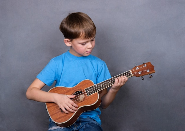 Cute european boy to learn to play guitar ukulele