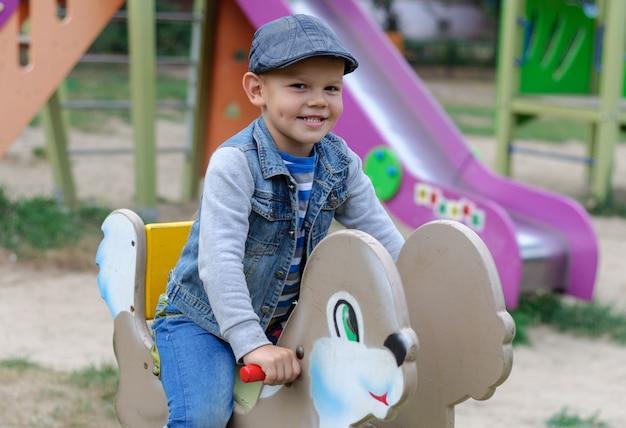 夏のブランコに乗って庭の遊び場でかわいいヨーロッパの少年