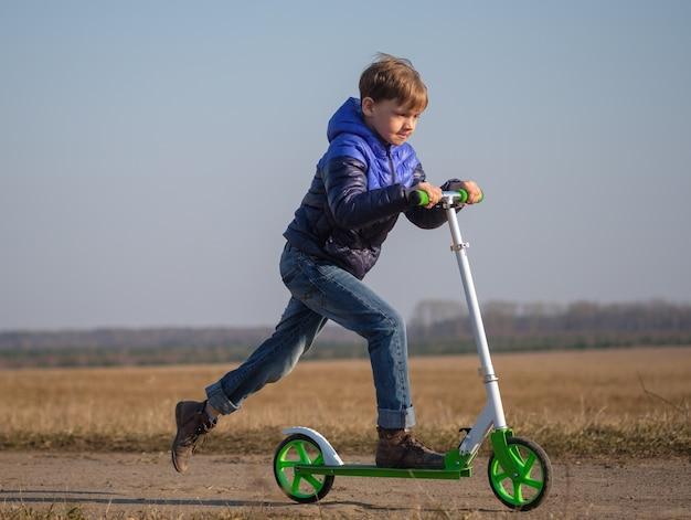 歩いている間スクーターに乗ってトリックをしているかわいいヨーロッパの少年