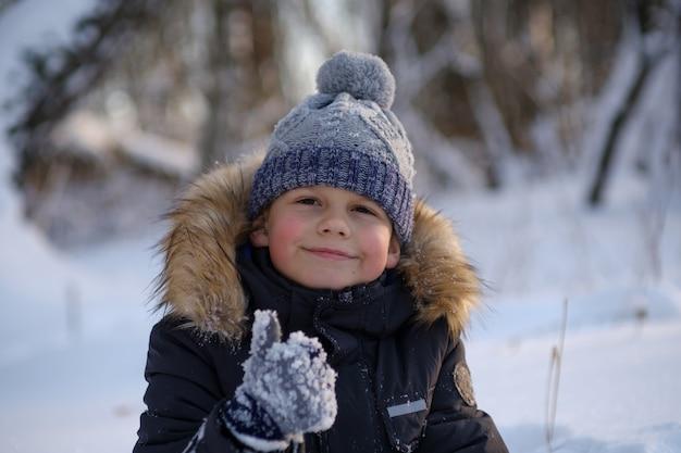 Симпатичный европейский мальчик показывает, как гуляет зимой в морозный солнечный день