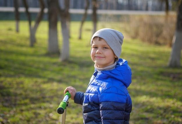 公園で夕方にスクーターとかわいいヨーロッパの少年