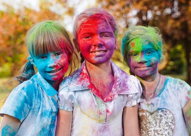 Cute european child girls celebrate indian holi festival with colorful paint powder on faces and body