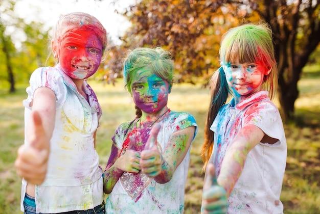 Милые европейские девочки-подростки празднуют индийский фестиваль холи красочной краской на лицах и теле