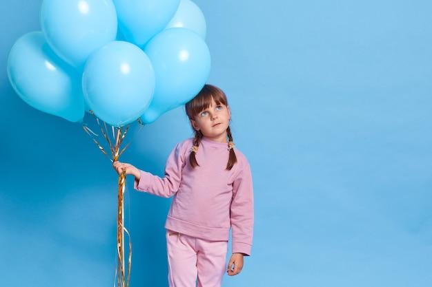 Carina bambina europea che indossa chiusura rosa, bambino con trecce che guarda con espressione facciale premurosa, sogna qualcosa di piacevole, tenendo un mazzo di palloncini di elio, contro il muro blu.