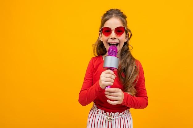 Милая европейская девушка поет в микрофон на желтом