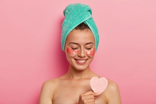 La simpatica signora europea gode del trattamento della pelle degli occhi, tiene la spugna cosmetica sul corpo nudo, ha un sorriso gentile, indossa un asciugamano da bagno avvolto, modelli al coperto. persone e concetto di bellezza.