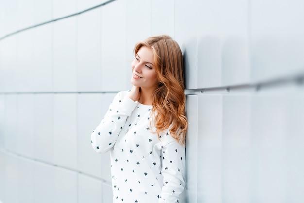 ファッショナブルな服を着たかわいいヨーロッパのポジティブな若い女性は、屋内の白いモダンな壁の近くに立って笑っています