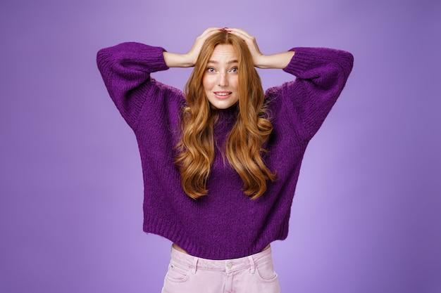かわいいヨーロッパの赤毛の20代の女性は、神経質に行動し、心配と不安で眉を上げる頭に手をつないで、困っているパニックは紫色の背景の上にポーズをとる計画を考えます。コピースペース