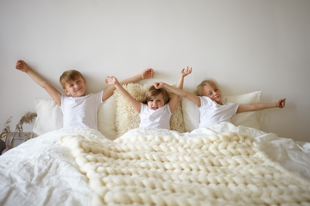 Cute european siblings enjoying slow lazy morning, doing stretches in parents' bedroom. three adorable casually dressed kids lazing together in bedroom, stretching arms, unwilling to get up