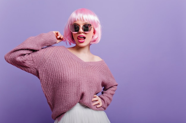 Cute european woman in colorful periwig posing with tongue out.  confident blissful girl with pink hair wearing glasses and purple sweater.