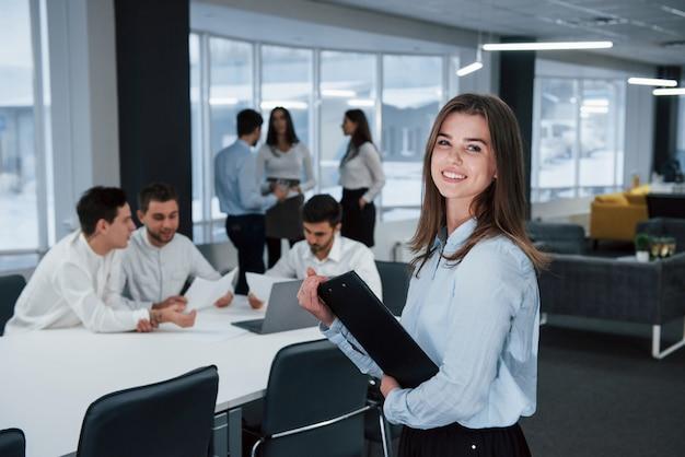 かわいいヨーロッパの女性。バックグラウンドで従業員とオフィスに立っている若い女の子の肖像画