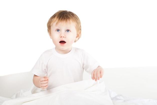 Милая возбужденная девочка в постели у себя дома над белой