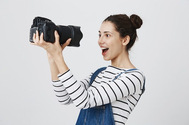 Il fotografo della ragazza carina ed eccitata riceve una nuova fotocamera professionale