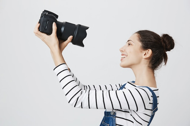 Cute and excited girl photographer taking selfie on professional camera