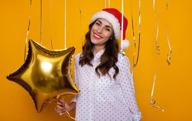 クリスマスと新年を祝っている間、孤立した黄色の背景にポーズをとって空気ヘリウム風船と赤いサンタ帽子のかわいい興奮した若い女性