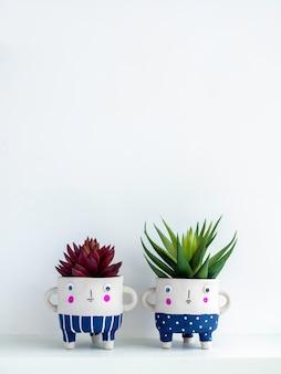 緑と赤の多肉植物を棚に並べたかわいい顔のセラミック植木鉢で、コピー スペース、垂直スタイルの白い壁に分離されています。 2 つの小さなモダンな diy セメント プランターのトレンディな装飾。