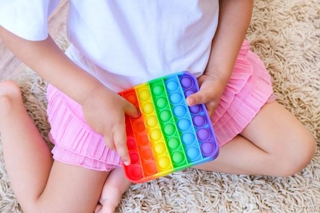 ポップイットのそわそわで遊んでいるかわいい顔のない子供。プッシュポップバブルフレキシブルフィジェット感覚玩具は、分泌物を提供し、子供の発達に適しています