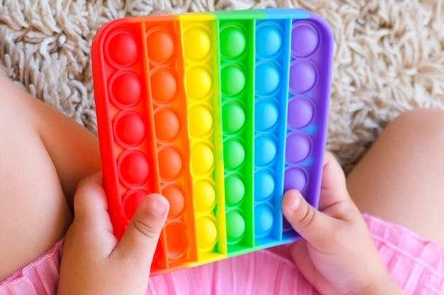 팝 잇 피젯을 가지고 노는 귀여운 얼굴 없는 아이. 푸쉬팝 버블 플랙시블 안절부절 감각장난감은 토출을 제공하고 아이의 발달에 좋습니다.